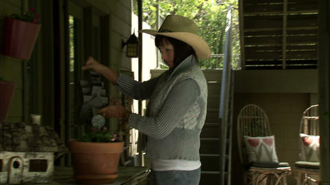 Lady watering her potted plants outdoors Footage