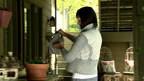 Lady watering potted flowers with a watering can Footage