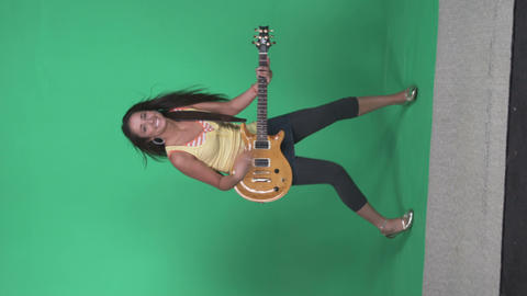 Full body shot of a girl dancing and strumming electric guitar Footage