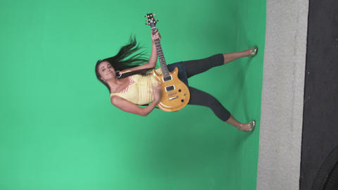 Full body shot of a girl holding an electric guitar and rocking out Footage