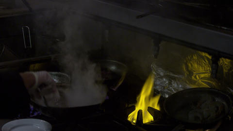 Kitchen worker cooking over a flaming stove Footage
