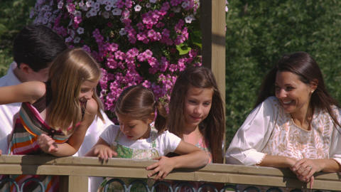 Family in a beautiful garden on a bridge Footage