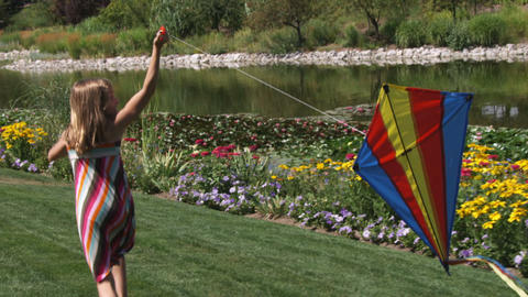 Slow motion shot of a girl playing with a kite in beautiful gardens Footage