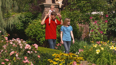 Clip of a young family walking through beautiful gardens Footage