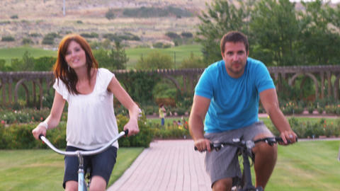 Slow motion shot of a young couple riding bikes through a beautiful garden Footage