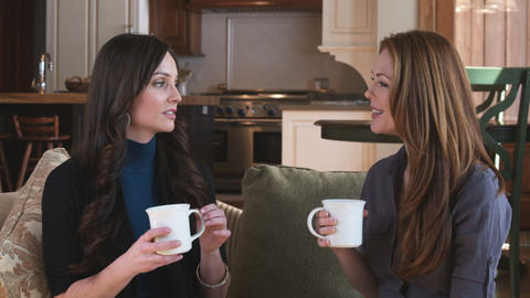 Two women talking on a couch with mugs Footage