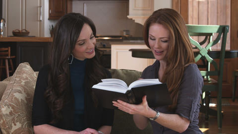 Dolly shot of two women discussing a book together Footage