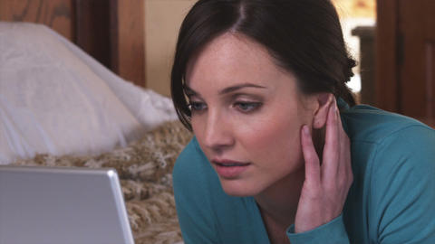 Woman in pajamas using a laptop on her bed Live Action
