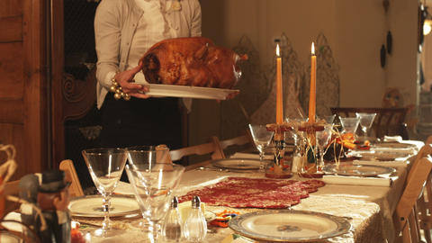 Woman serving a turkey at a decorated Thanksgiving table Live Action