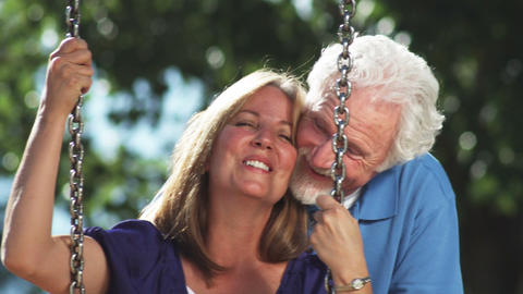 Happy older couple on a park swing Live Action
