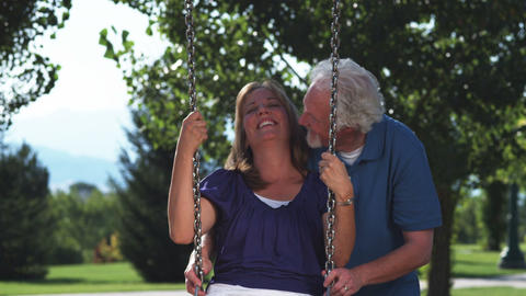 Older man pushing his wife on a swing Live Action