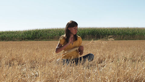 Woman in a wheat field relaxes while holding strands of wheat Footage