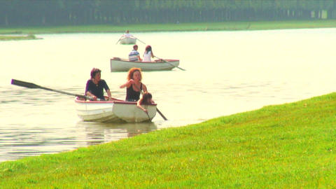 Two women and a child row a boat in a pond at Versailles, France Live Action