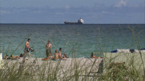 People on a beach in Miami and a cargo ship out in the ocean Live Action