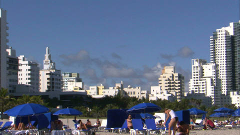 People laying on a beach in Miami with hotels in the background Live Action