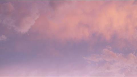 Pinkish clouds slowly move and rearrange in the sky Footage