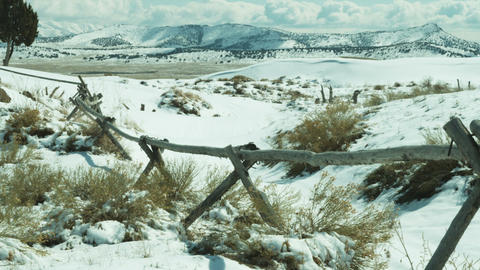 Pan of rural fence among snowy hills Footage