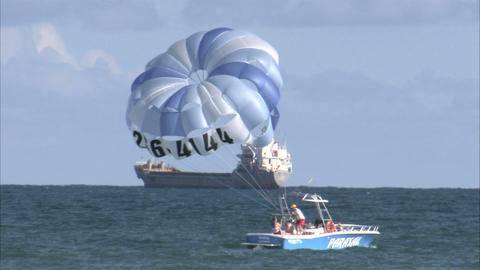 Parasail boat in the ocean with cargo ship in the background Live Action