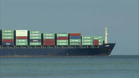 Large cargo ship coming into view on the ocean Live Action