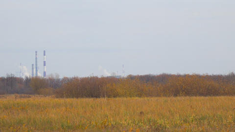 Smokestacks in distance on the background of autumn meadows ビデオ