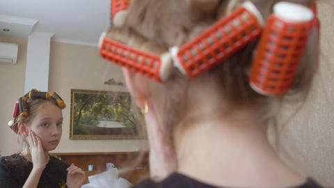 Teenager girl with curlers on hair applying tone cream front mirror in bedroom ビデオ
