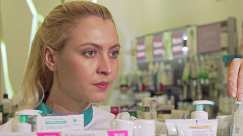 Female pharmacist organizing products on a shelf, working at drugstore Footage