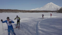 Skiers running along ski track on background of volcano ビデオ