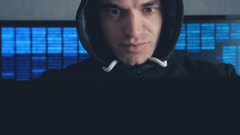 Wanted Male hacker in hood working on a computer in a dark office room. Shot on Live Action