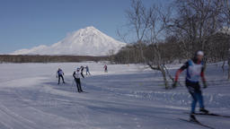 Skiers running along winter ski track on background of volcano Footage