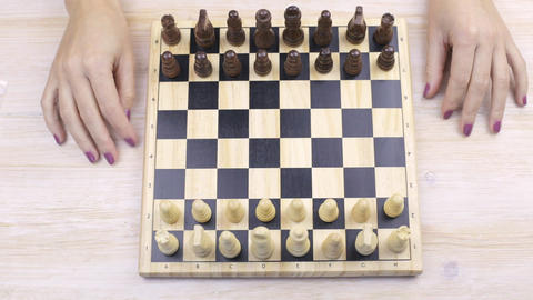 Chess and female hands on a table Archivo