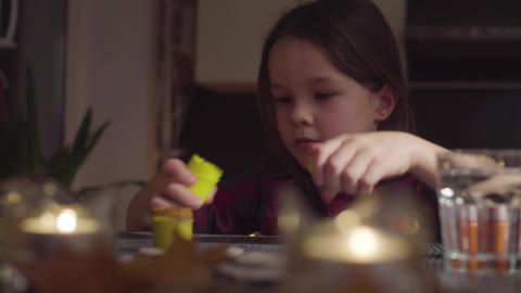 The girl opens the jars of paint and begins to paint the bat Footage