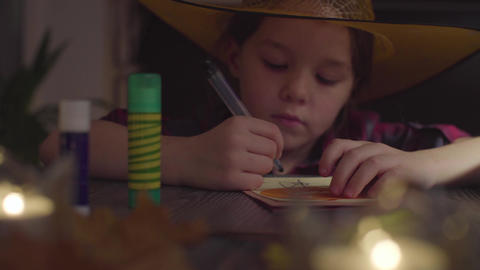 The girl drawing spider web on a card. Preparing for the celebration of Footage