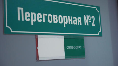 Female hand moves plate to occupied on door with russian text meeting room 영상물