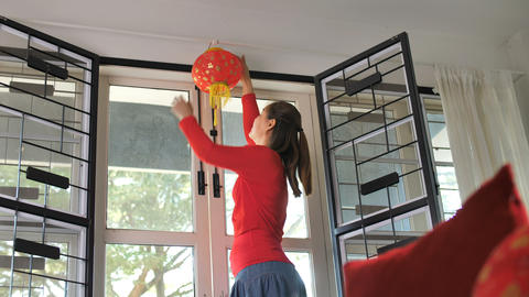 Slow motion, Happy Asian woman decorate her house for Chinese New Year Footage