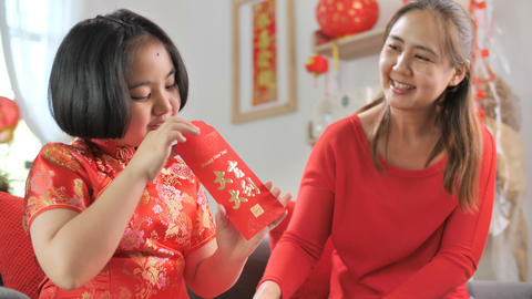Happy Asian woman give the red pocket envelope to children in Chinese New Year Live Action