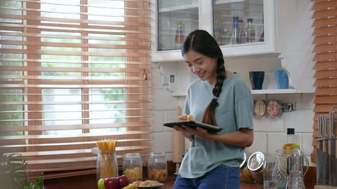 Young asian woman using tablet and eating bread. technology, social network, Footage