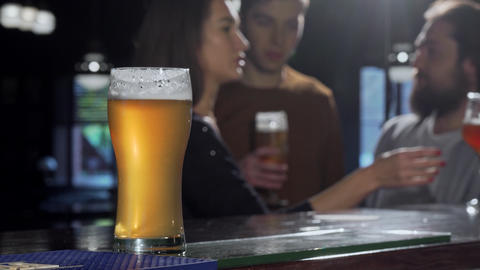 Selective focus on a beer glass, people drinking at the pub on the background ライブ動画