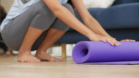 Young asian woman rolling yoga mat to perform yoga asanas safely and comfortably Live Action