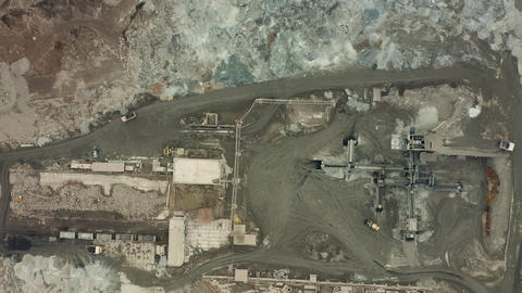 Aerial view of opencast mining quarry with lots of machinery at work - view from Footage