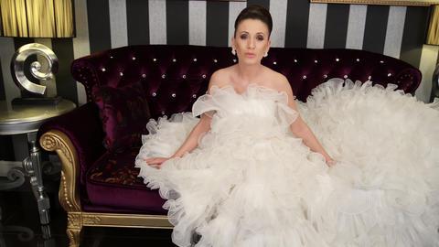 Fashionable woman wearing elegant white dress sings sitting on large black sofa ビデオ