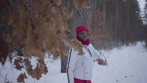 African american girl walking through winter forest. Beautiful girl in warm Footage