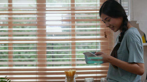 Young asian woman using mobile phone at home and drinking coffee ビデオ