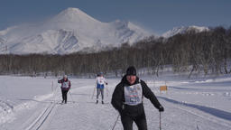 Skiers running along winter ski track on background of active volcanoes GIF