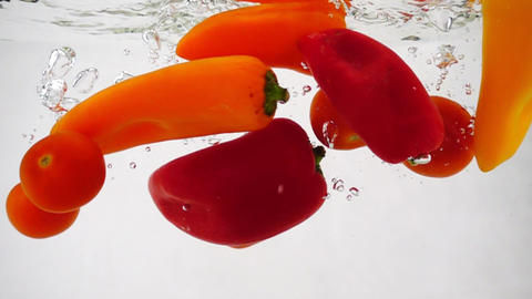 Sweet peppers and cherry tomatoes float in the water on a white background Footage