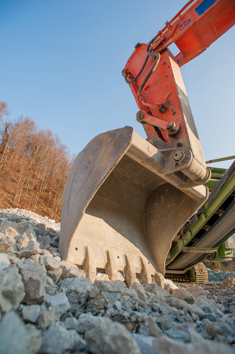 bulldozer at work while charging trucks in gravel pit Photo