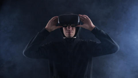 Futuristic man in hood Wearing VR Headset. Futuristic man using Virtual Reality Live Action