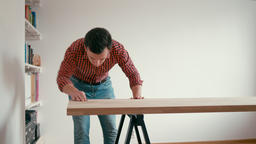 Young Man is Making Oak Wooden Table at Home. Man is Rubbing Desk with Sandpaper 영상물
