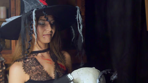 Halloween witch close-up with a staff of a human skull. Maliciously smiles Footage