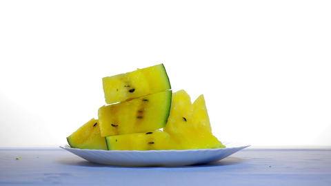 On the table slices of yellow watermelon. Another slice falls from above Live Action