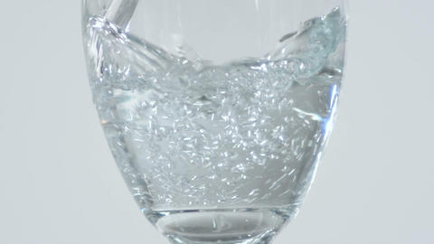 Close up of a stemmed glass being filled with pouring water Footage